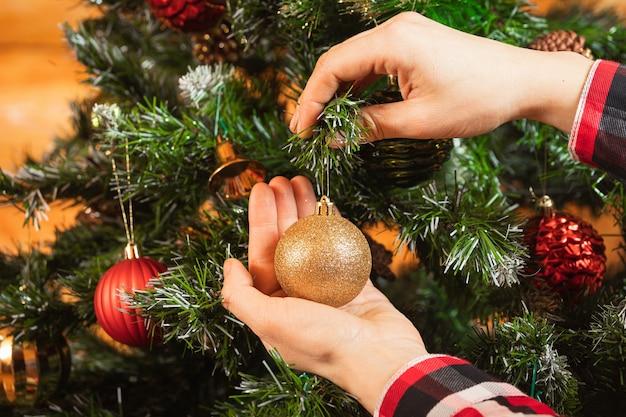 格子縞のシャツを着た女性のクローズアップは、クリスマスツリーに美しい光沢のある金のボールを掛けます
