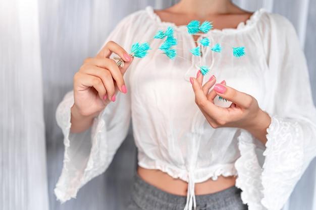 理想的なピンクのマニキュアの白いブラウスと、茎に青い花を持っている彼女の手の中の女性のクローズアップ。ケアとスパ