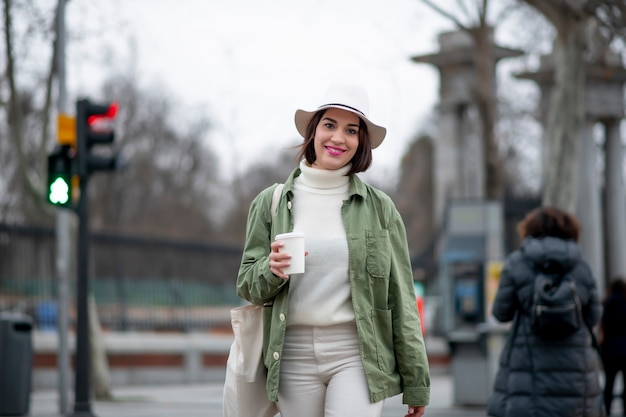 通りを歩きながらコーヒーを飲む白い帽子の女性のクローズアップ