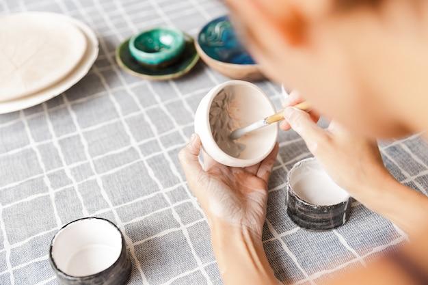 Крупным планом женщины, делающей керамическую и гончарную посуду в мастерской, работая с глиной