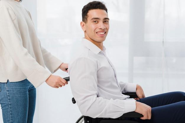 휠체어에 앉아 웃는 젊은 남자를 밀고 여자의 근접 촬영