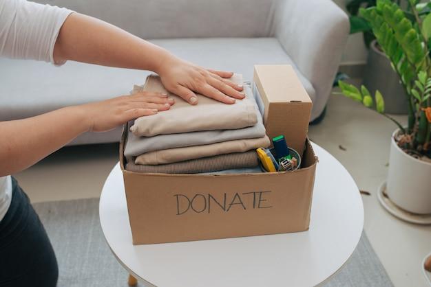 Крупный план женщины кладет одежду в ящик для пожертвований