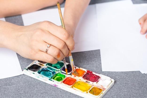 Крупный план руки женщины и ребенка берут акварельные краски в старом пакете, палитре красок. творчество и увлечения для взрослых и детей