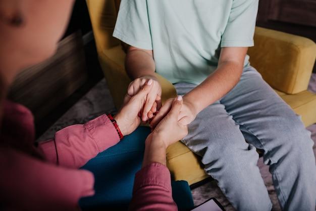 女性の握りしめられた手と子供の手のクローズアップ