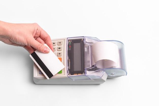 상점에서 구매 또는 서비스 비용을 지불하기 위해 금전 등록기 위에 은행 카드를 들고있는 여성의 손 클로즈업