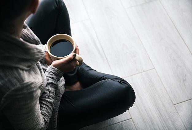 ホットコーヒーのカップを持っている女性の手のクローズアップ。ファッション、レジャー