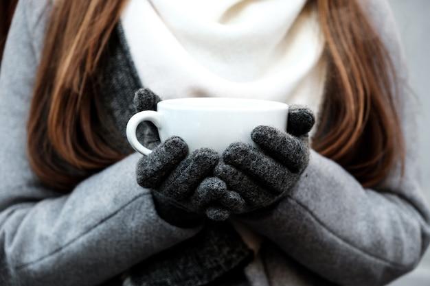 뜨거운 커피 한 잔을 들고 있는 여성의 손 클로즈업.