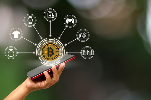 ホログラム、ビットコインのシンボル、ビジネスアイデアのオンライン取引アイコンとスマートフォンを持っている女性の手のクローズアップ。暗号通貨と将来の技術。