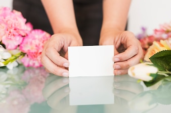 Close-up of a woman's hand holding blank white visiting card over desk