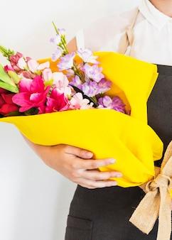 新鮮な花の花束を握っている女性の手のクローズアップ