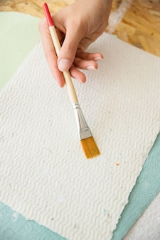 Close-up of a woman's hand holding paintbrush over white paper
