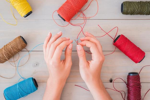 木製のテーブルの針に青い糸を挿入する女性の手のクローズアップ