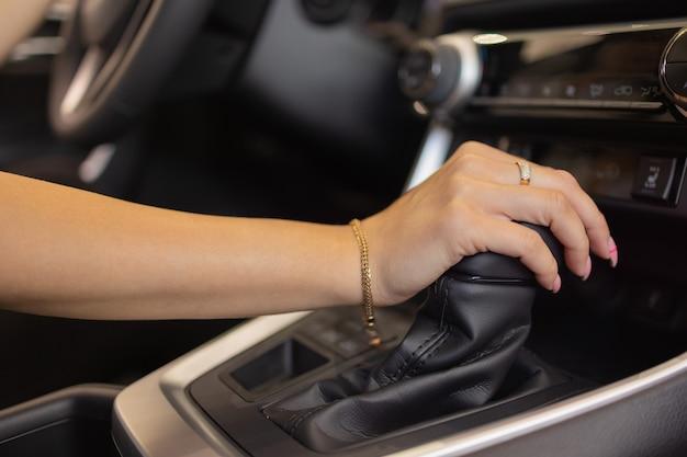 現代の車のハンドルに女性の手のクローズアップ。