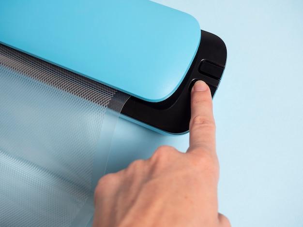 青い真空パッカーのボタンを押す女性の手のクローズアップ。食品の保存と保管のための装置の概念