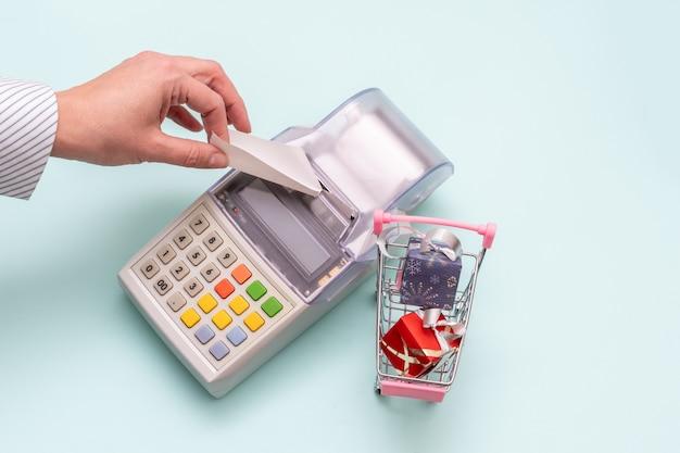 Крупный план руки женщины, отрывающей чек от старого кассового аппарата рядом с тележкой с упакованными коробками с подарками