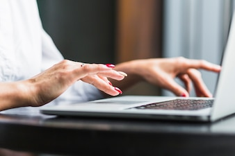 Close-up of a woman's hand using laptop