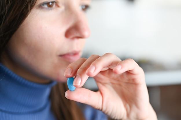 薬を飲んで水のガラスと女性の手のクローズアップ。ボックスの丸薬。コロナウイルス治療の概念