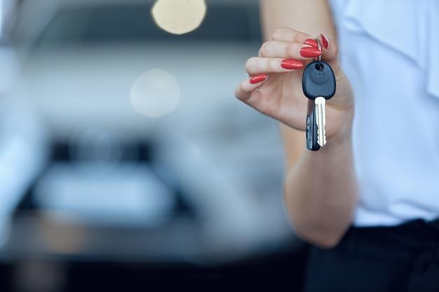 새 차 열쇠를 들고 있는 여성의 손 클로즈업.
