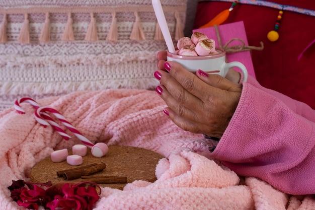 Крупным планом - руки женщины в розовой пижаме, держащей горячий шоколад с зефиром в керамической чашке. праздники и люди концепции