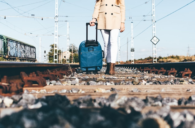 철도 트랙을 따라 그녀의 가방과 함께 걷는 여자의 다리 닫습니다.