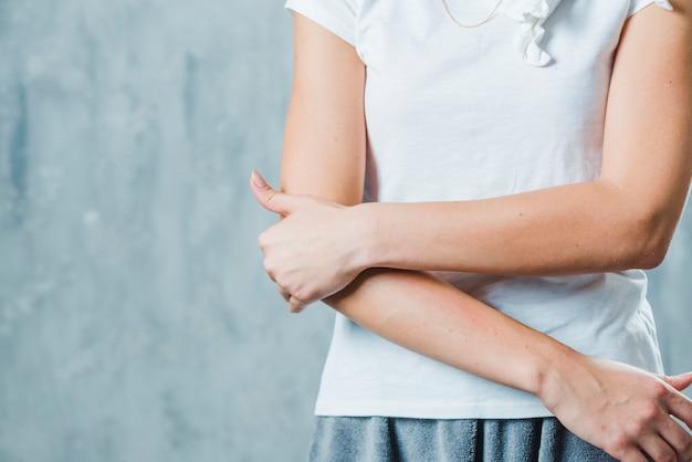그녀의 팔꿈치에 통증이있는 회색 벽에 서있는 여자의 근접 촬영