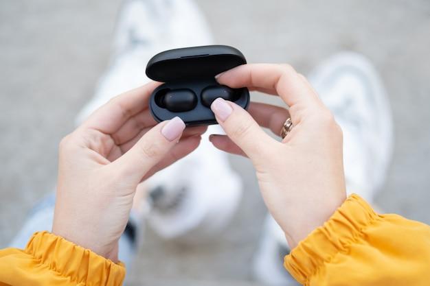 충전 상자에서 검은색 무선 이어폰을 꺼내는 여성의 클로즈업. 휴대용 가제트 헤드폰을 만지는 여성의 손.