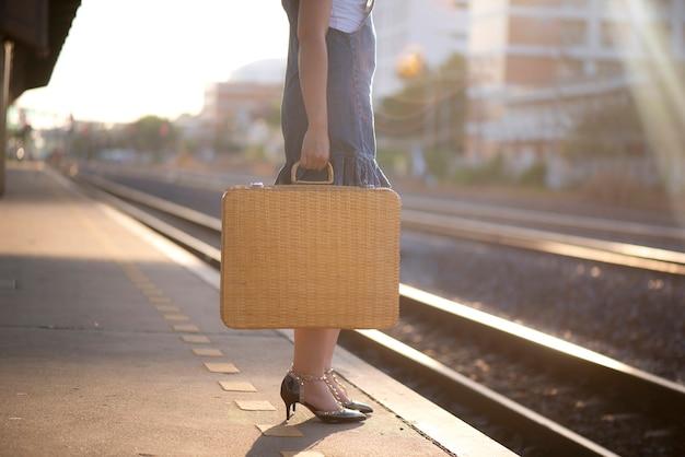 기차역에서 기차를 기다리는 가방으로 여행하는 여자의 닫습니다