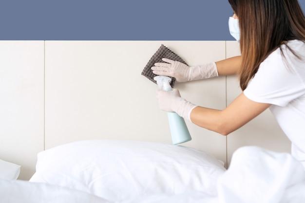 Крупным планом женщины в маске и перчатках, дезинфицирующих поверхность Premium Фотографии
