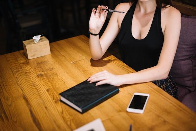 Крупным планом женщина с дневником и сотовый телефон на столе в ресторане