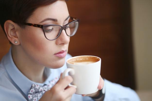 短い髪と彼女の手でコーヒーカップを持つ女性のクローズアップ