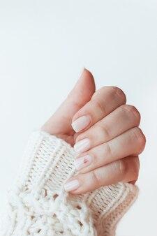 Крупным планом женская рука с идеальным естественным нейтральным нежным маникюром на белом фоне