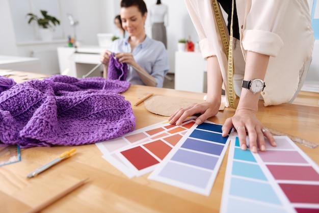 그녀의 동료가 보라색 실로 뜨개질하는 동안 여러 계획에 그녀의 손을 가지고 그중 하나를 선택하는 여성의 닫습니다