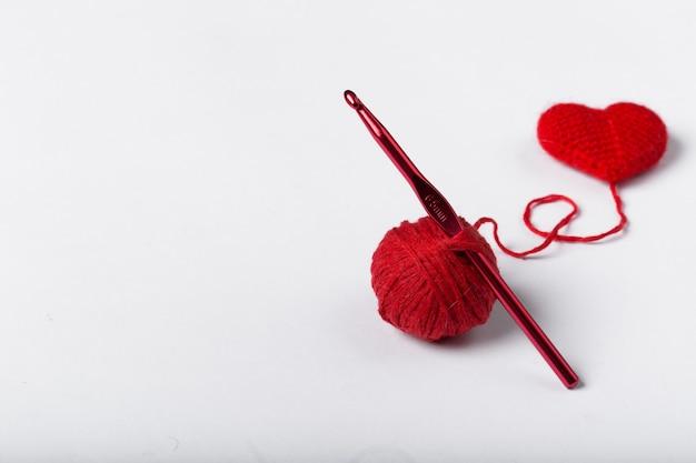 白い背景の上の羊毛のボールとハートの形のクローズアップ。ハート型のウール糸。かぎ針編みが大好きです。