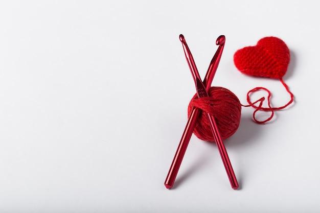 Закройте вверх шарика шерсти и формы сердца на белой предпосылке. шерстяная пряжа в форме сердца. любовь крючком.