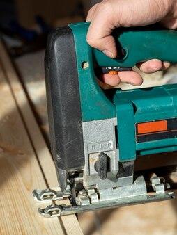 電気ジグソーで木の板を鋸で挽く労働者のクローズアップ