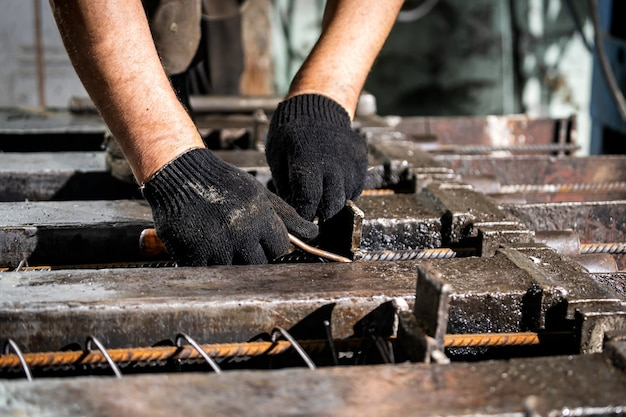 Крупным планом - рабочий в перчатках с проволокой, связывающей арматуру на производстве.