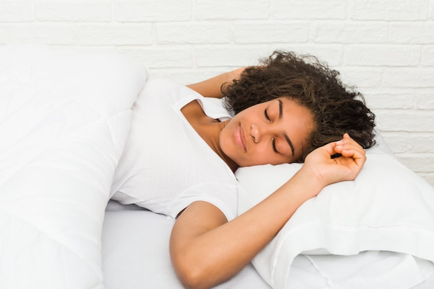 Крупным планом молодой афроамериканец устал женщина спит на кровати