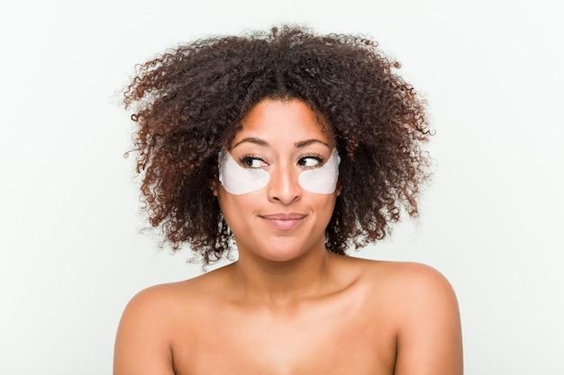 눈 피부 치료를 가진 젊은 아프리카 계 미국인 여자의 닫습니다 프리미엄 사진
