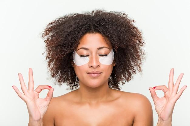 눈 피부 치료를 가진 젊은 아프리카 계 미국인 여자의 닫습니다