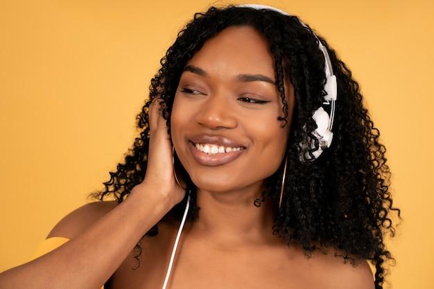 孤立した黄色の背景に立ってヘッドフォンで音楽を聴いて楽しんでいる若いアフロ女性のクローズアップ。