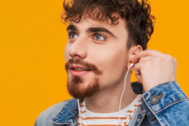 고립 된 이어폰으로 음악을 듣고 부담없이 옷을 입고 젊은 수염 난된 남자의 닫습니다