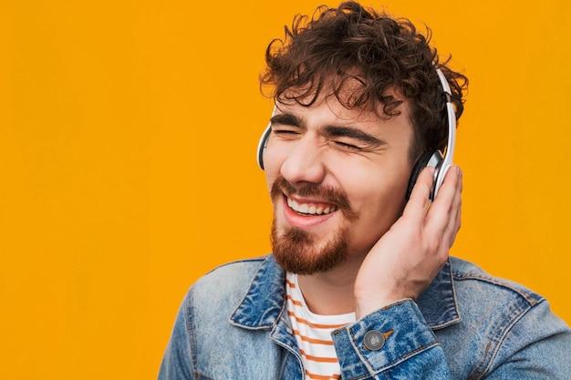 고립 된 헤드폰으로 음악을 듣고 부담없이 옷을 입고 젊은 수염 난된 남자의 닫습니다