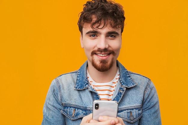 Крупным планом молодой бородатый мужчина, небрежно одетый с помощью мобильного телефона изолированы