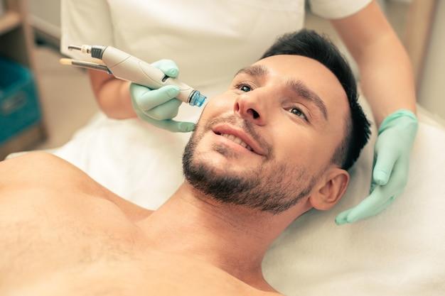 Крупным планом молодой бородатый мужчина выглядит довольным современным инструментом рядом с его лицом, питающим кожу
