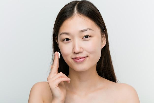 Закройте молодой красивой и естественной азиатской женщины, применяя увлажняющий крем