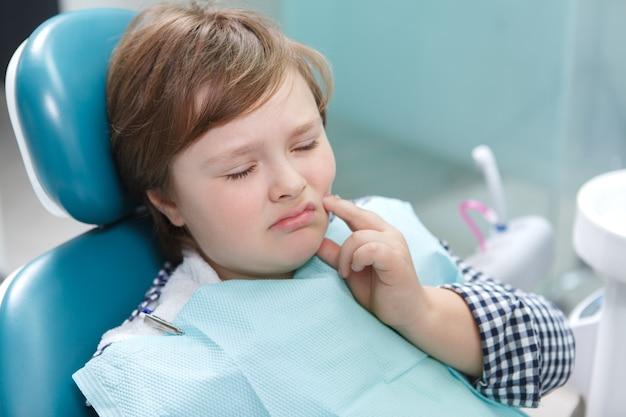 Крупным планом мальчика с зубной болью, сидящего в стоматологическом кресле в офисе стоматолога