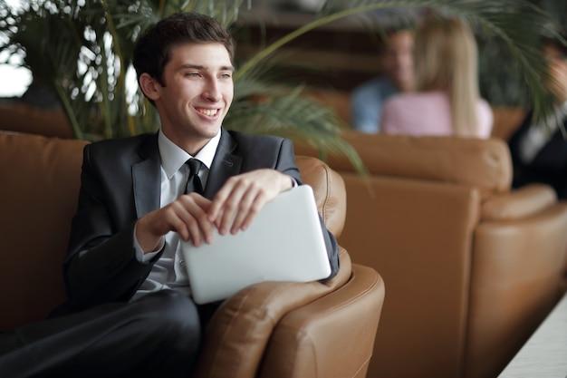 Крупным планом молодой бизнесмен с помощью цифрового планшета, сидя в холле банка.