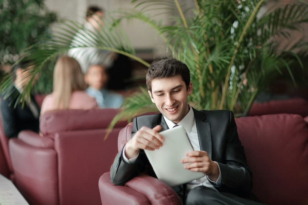 은행 로비에 앉아 디지털 태블릿을 사용하는 젊은 사업가의 클로즈업.