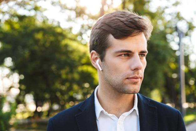 イヤホンを身に着けて、屋外を歩いている青年実業家のクローズアップ