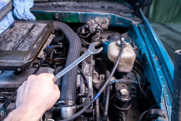 Конец-вверх молодого ремонтника автомобиля держа ключ в его руке и около для того чтобы отремонтировать автомобиль под клобуком автомобиля. концепция автосервиса и автосервиса